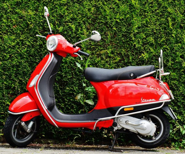 red-and-black-moped-scooter-beside-green-grass-159192